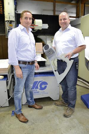 Jürgen und Bernd Hopf mit dem neuen Seitenteil vor der Beschnittmaschine.