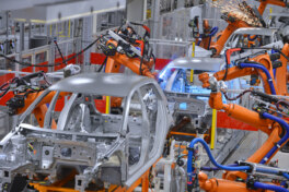 KI: robots welding in an automobile factory
