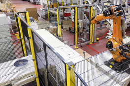 Die Roboter entnehmen die fertigen Folienrollen den Rollenschneidanlagen und legen sie auf einen Bandförderer.