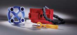 Der Freeformer nutzt bei Bauteilen mit beweglichem Gelenk wie dem orangenen Schlüsselanhänger eine zweite Austragseinheit für den Aufbau von Stützstrukturen, die sich später leicht entfernen lassen.
