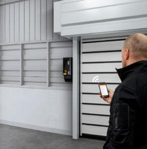 Mann öffnet Industrietor mit dem Smartphone