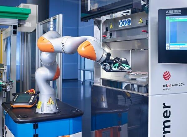 Bild 4: Auf der Fakuma 2015 präsentiert Arburg erstmals die automatisierte additive Fertigung. Ein Sieben-Achs-Roboter bestückt den Bauraum des Freeformers, der über eine Euromap-67-Schnittstelle verfügt.